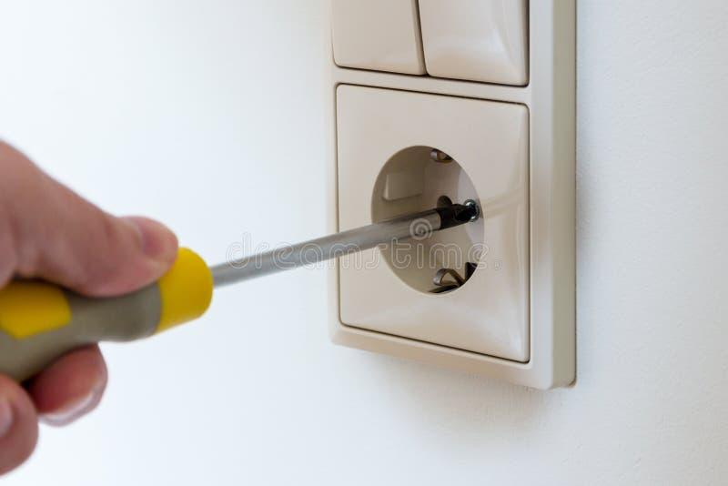 Installando uno sbocco elettrico sulla parete fotografie stock