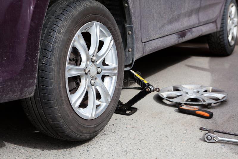 Installant la roue de voiture avec niveler le cric de main, partie antérieure de levage de véhicule, vue en gros plan images stock