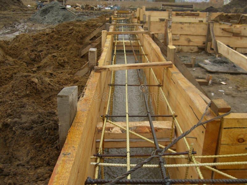 Installant les formes en bois pour verser le fossé concret de base renforcé avec le renfort fait de fibre de verre photographie stock