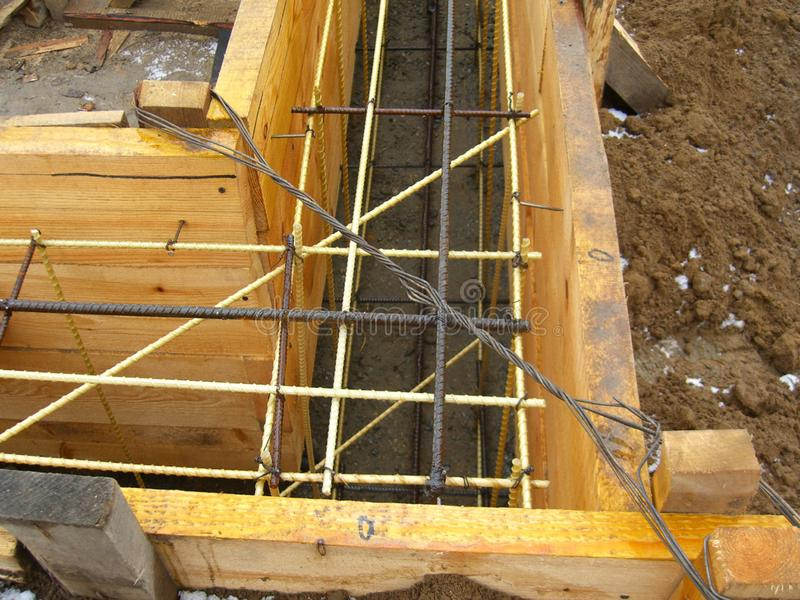 Installant les formes en bois pour verser le fossé concret de base renforcé avec le renfort fait de fibre de verre image stock
