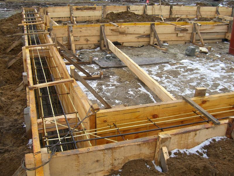 Installant les formes en bois pour verser le fossé concret de base renforcé avec le renfort fait de fibre de verre photo stock