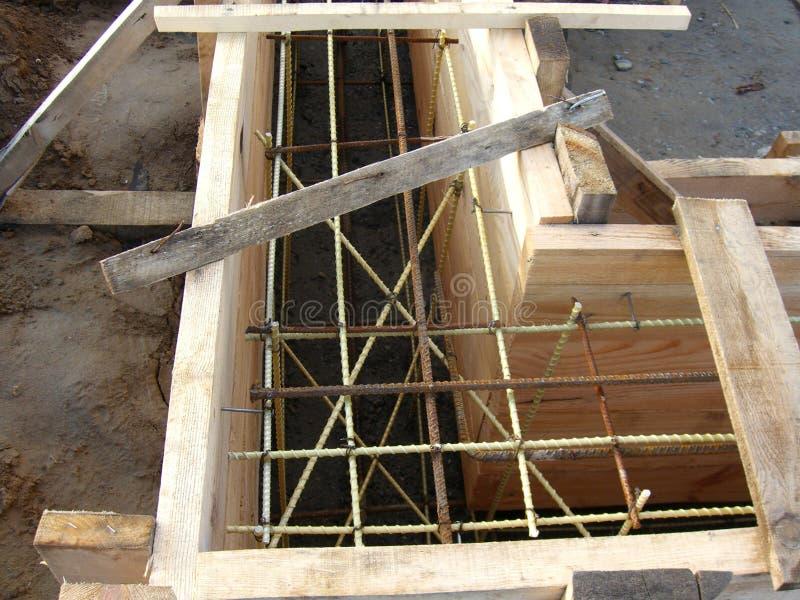 Installant les formes en bois pour verser le fossé concret de base renforcé avec le renfort fait de fibre de verre photos libres de droits
