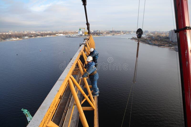 Installateurs die kraanbalk vast aan de mast van torenkraan werken stock fotografie