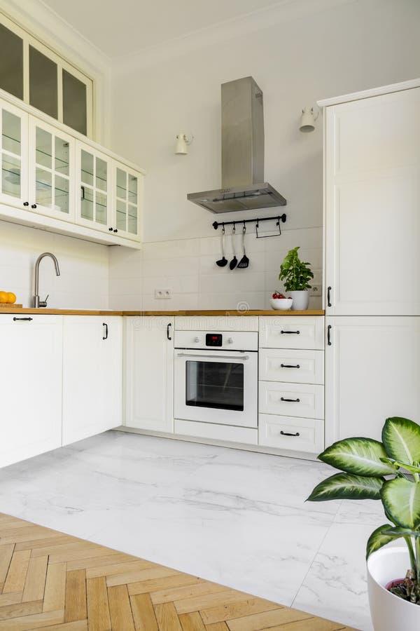 Installatie in eenvoudig wit keukenbinnenland met zilveren kooktoestelkap royalty-vrije stock afbeeldingen