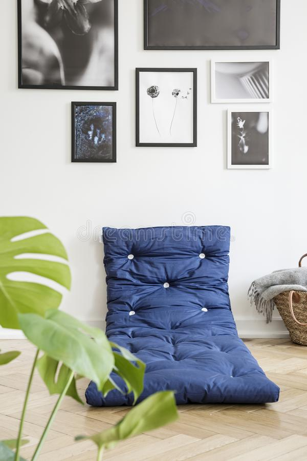 Installatie en blauwe matras op de vloer in wit slaapkamerbinnenland met galerij van affiches Echte foto royalty-vrije stock foto
