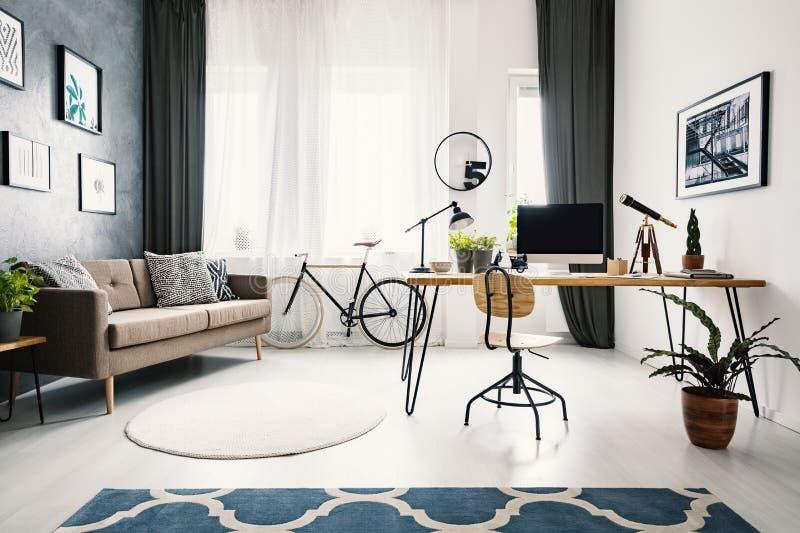 Installatie en houten stoel bij bureau in helder flatbinnenland met stock foto