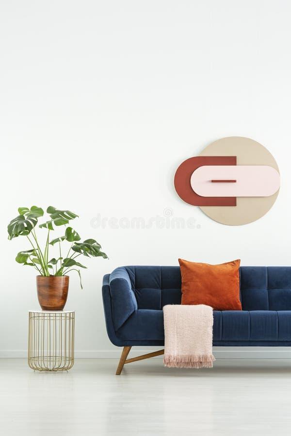 Installatie op lijst naast blauwe sofa met rood hoofdkussen in wit woonkamerbinnenland met affiche Echte foto stock foto's