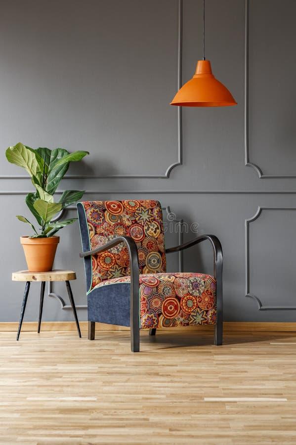 Installatie op lijst naast gevormde leunstoel onder oranje lamp in g stock afbeelding