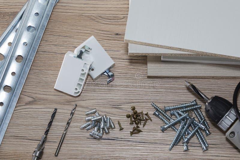 Installatie van spaanplaatmeubilair in een timmerwerkworkshop Toebehoren en hulpmiddelen voor timmerlieden stock afbeeldingen