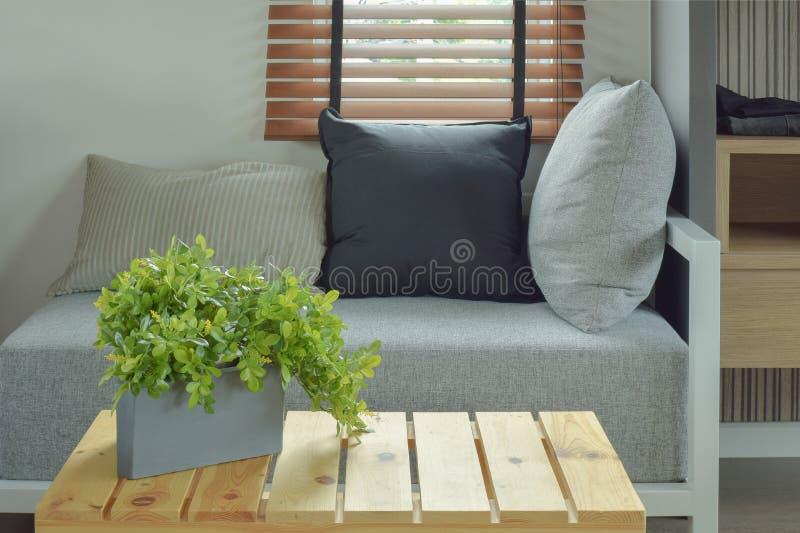 Installatiepot op centrum houten lijst en zetel op z'n gemak royalty-vrije stock afbeelding