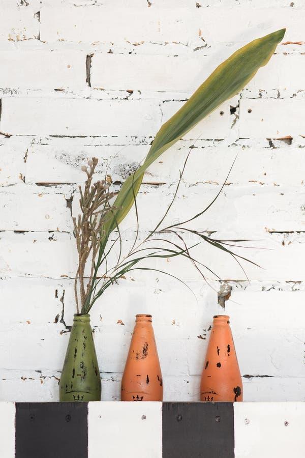 Installatiepot, tak, bloemen, met de hand gemaakte flessendecoratie op witte bakstenen muurachtergrond royalty-vrije stock afbeelding