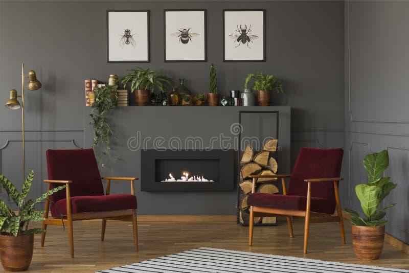 Installaties en rode leunstoelen in grijs woonkamerbinnenland met post stock afbeelding