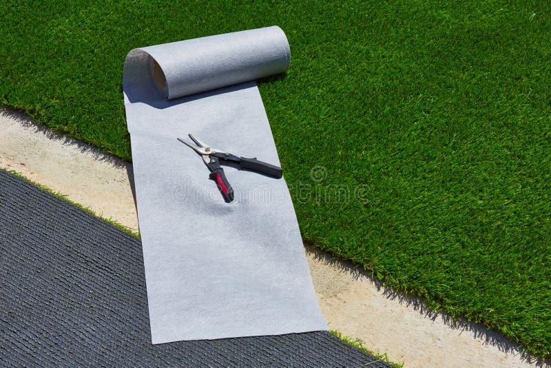Installation artificielle de gazon d'herbe dans le jardin avec des outils photographie stock