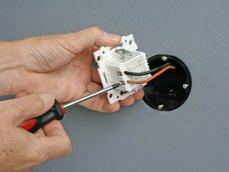 Installation av en dunklare strömbrytare i en vägghålighet royaltyfria foton