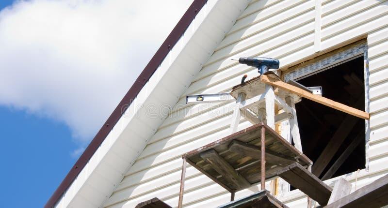 Installation av en siding på ett hus mot himlen arkivfoton
