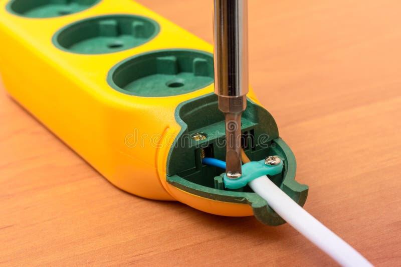 Installation av ett nytt uttag med en skruvmejsel, elektriskt arbete royaltyfri foto