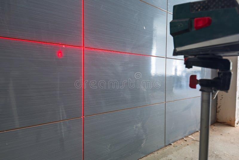 Installation av nya tegelplattor på väggen royaltyfri foto
