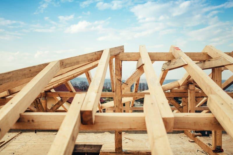 Installation av strålar och timmer på konstruktionsplatsen Byggande av strukturen för takbråckbandsystem av det nya bostads- huse royaltyfria bilder