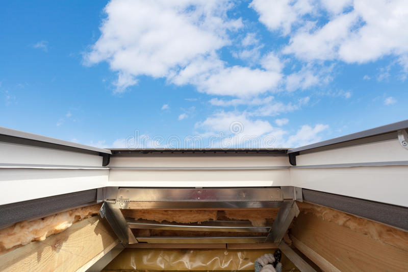 Installation av takfönstertakfönstret i nytt modernt passivt trähus mot blå himmel arkivbilder
