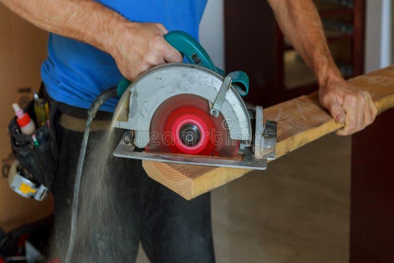 installation av trä i snickaren för man för konstruktion för nytt hus som den stiliga använder en cirkelsåg, medan installera trä arkivfoto