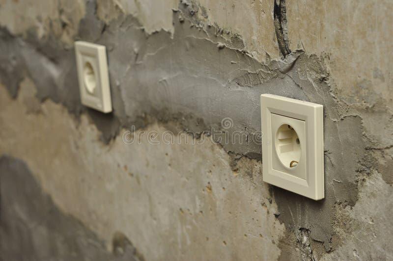 Installation av uttag under reparation i nya konkreta tomma väggar royaltyfria foton