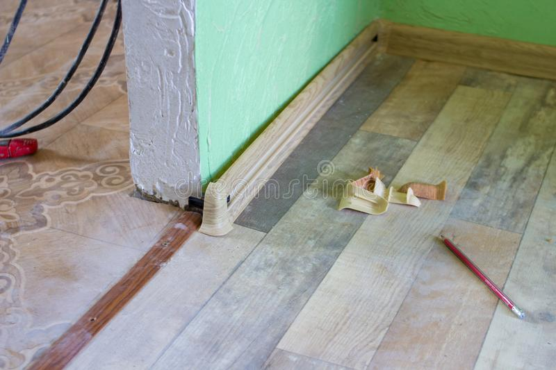 Installation of baseboards. Skirting decoration on the wall mount linolium stock image
