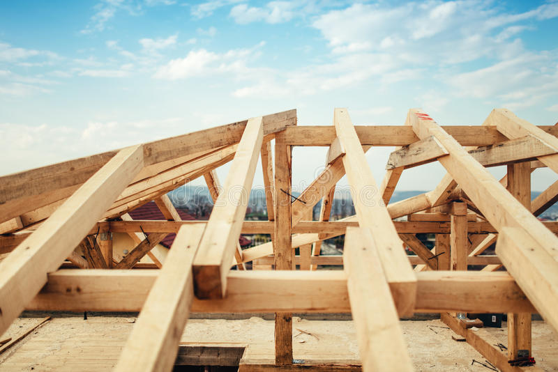 Installation of beams and timber at construction site. Building the roof truss system structure of new residential house royalty free stock images