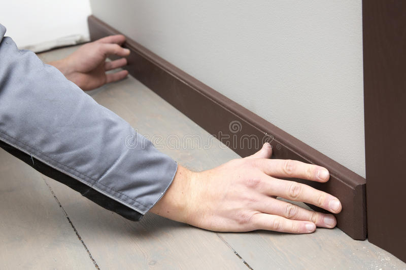 Installation of a brown wooden baseboard. At the bottom of the wall royalty free stock images