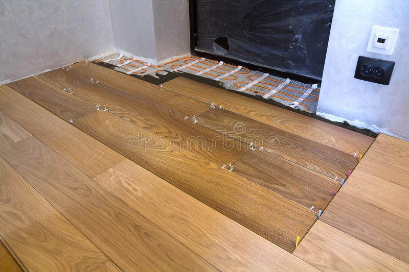 Installation of ceramic tiles and heating elements in warm tile floor. Renovation and improvement concept. Installation of ceramic tiles and heating elements in royalty free stock photography