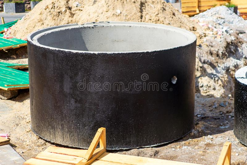 Installation of concrete sewer wells in the ground at the construction site. The use of reinforced concrete rings for cesspools, royalty free stock photo
