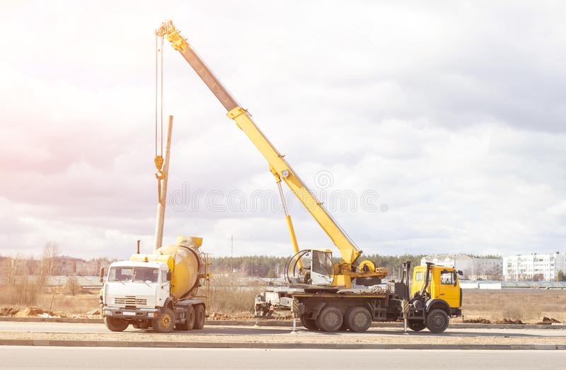 Installation and construction of lighting lamps on the new road using a truck crane and cement truck, the sun, copy space building. Installation and construction royalty free stock images