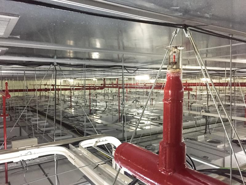 Installation d'extinction automatique d'incendie avec les tuyaux rouges sur l'unité de filtrage de fan, arroseuse automatique du photographie stock libre de droits