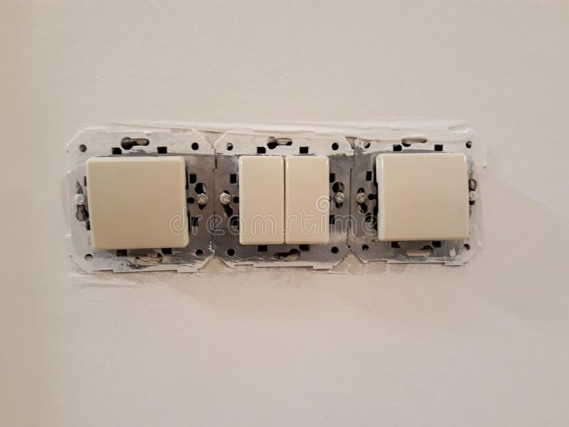 installation d'un commutateur électrique dans une maison sous la rénovation sur le mur images stock