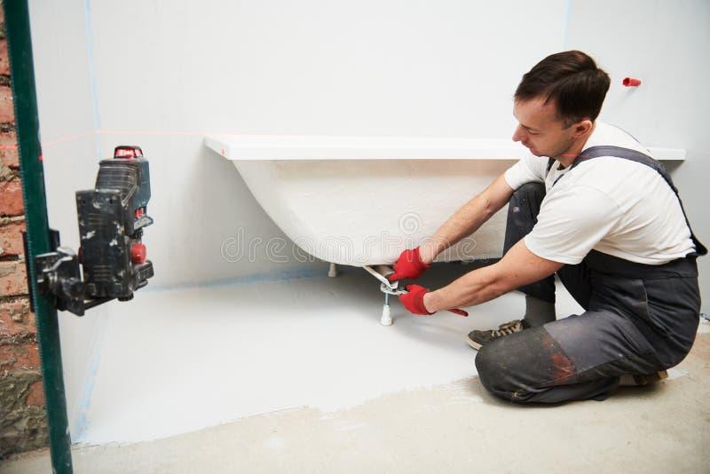 Installation de Bathtube plombier installant et montant le bain avec le niveau de laser image stock