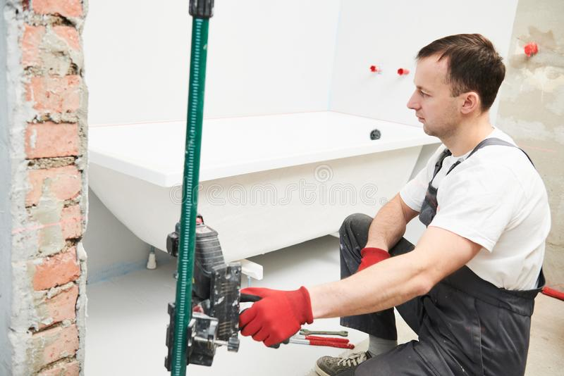 Installation de Bathtube plombier installant et montant le bain avec le niveau de laser photo stock