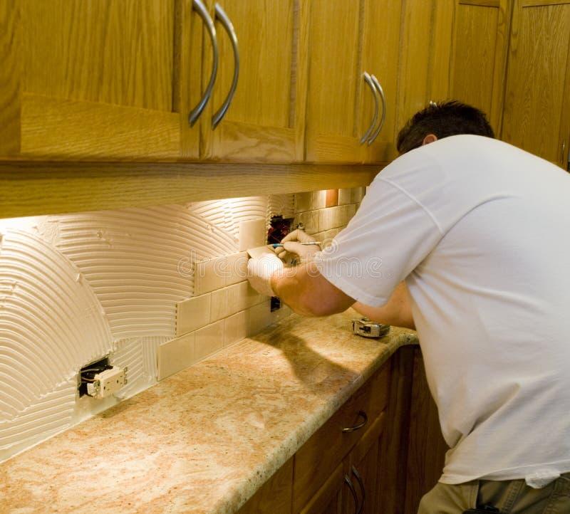 Installation de carreau de céramique sur le backsplash 12 de cuisine photographie stock