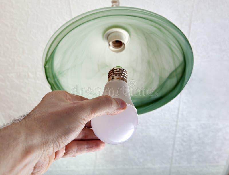 Installation de l'ampoule de LED dans le plafonnier, main tenant la lampe photos stock