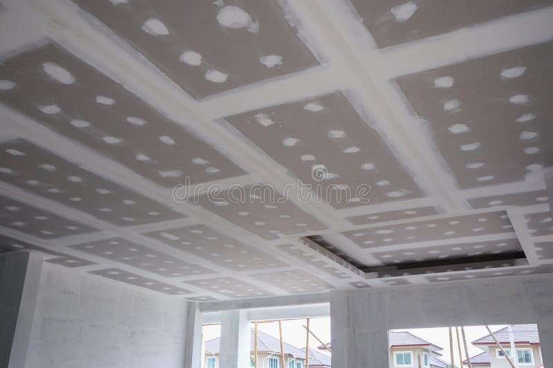 Installation de panneau de gypse de plafond au chantier de construction photos libres de droits