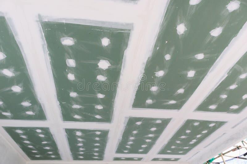 Installation de panneau de gypse de plafond au chantier de construction images libres de droits