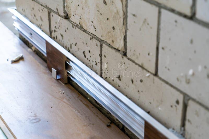 Installation der versteckten Fussleiste in dem Anfangsstadium von Fertigungsarbeiten Hauptreparatur lizenzfreies stockbild