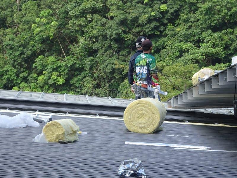 Installation des Metallplattform-Dachblattes durch Bauarbeiter stockbild