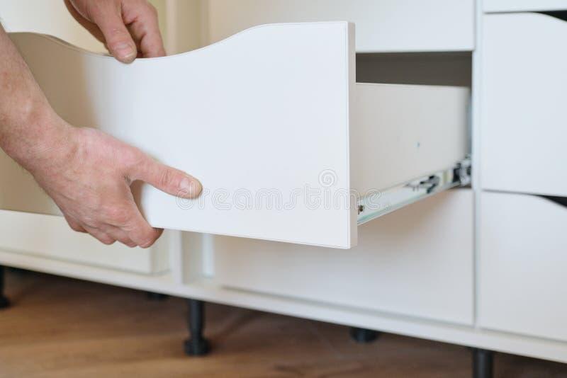 Installation des meubles Le plan rapproché des travailleurs remettent et des petits groupes de meubles images stock