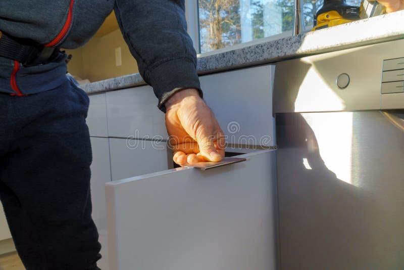 Installation of door handles on kitchen cabinets with a screwdriver. Installation handles of door on kitchen white cabinet with a screwdriver work furniture wood stock photo