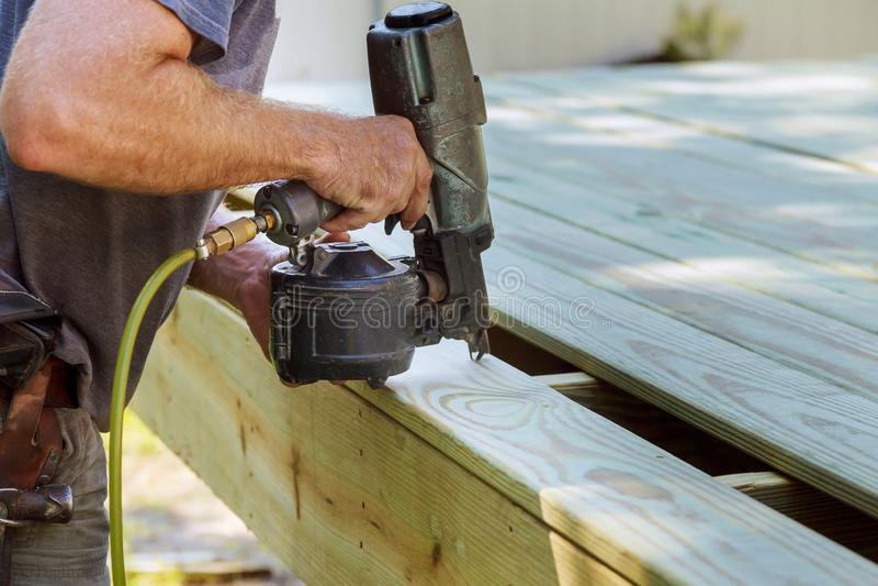 Installation du bois sur la plate-forme, homme de construction de patio à l'aide de l'arme à feu pneumatique image libre de droits