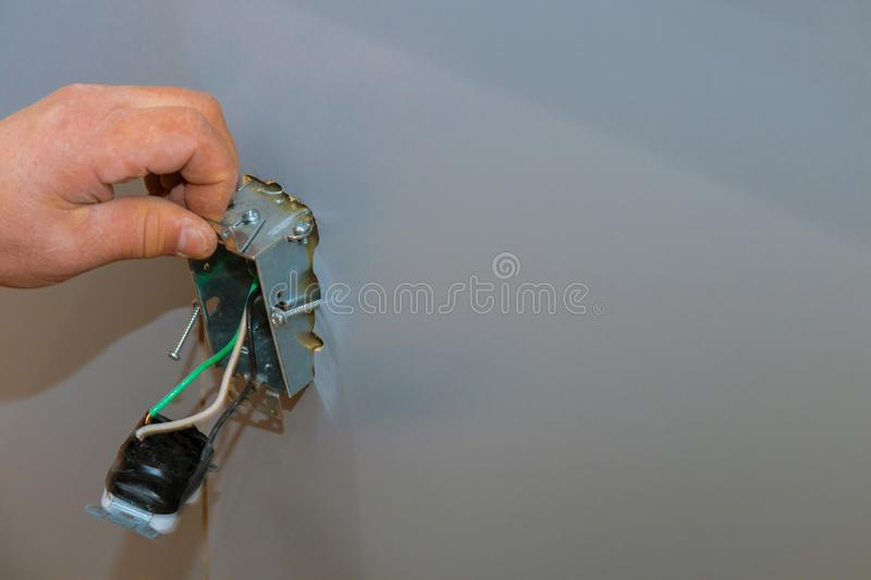 Installation of electrical sockets in hand of electrician installing wall outlet. Installation of electrical sockets in closeup of hand of electrician installing royalty free stock image
