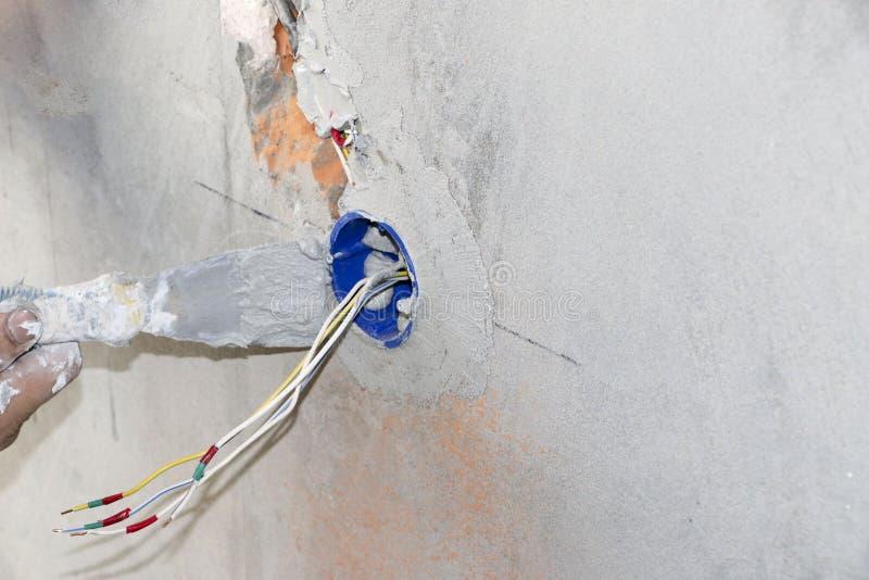 Installation för vägghålighet Arbete på installation av elektriska uttag Elektrikeren förbereder de passande uttagen för lednings arkivbilder