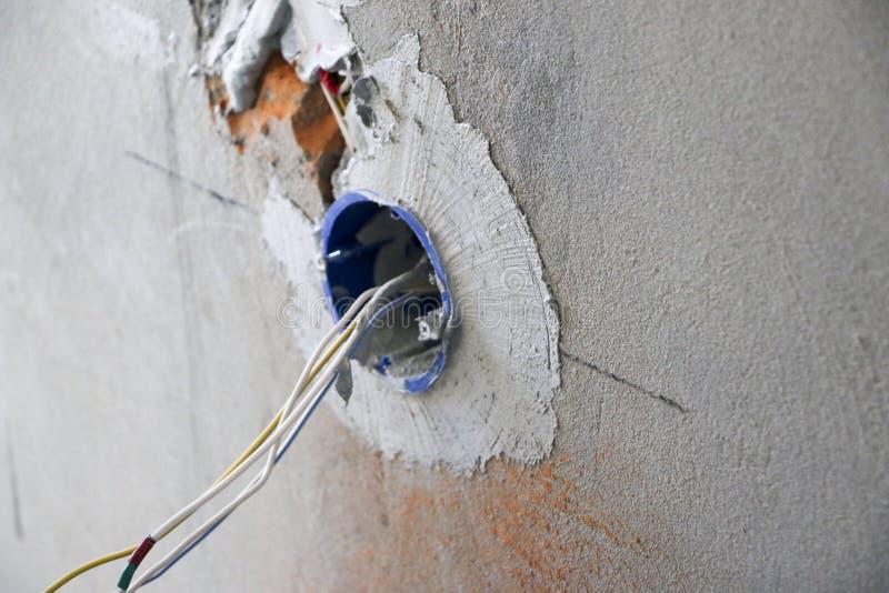 Installation för vägghålighet Arbete på installation av elektriska uttag Elektrikeren förbereder de passande uttagen för lednings royaltyfria bilder
