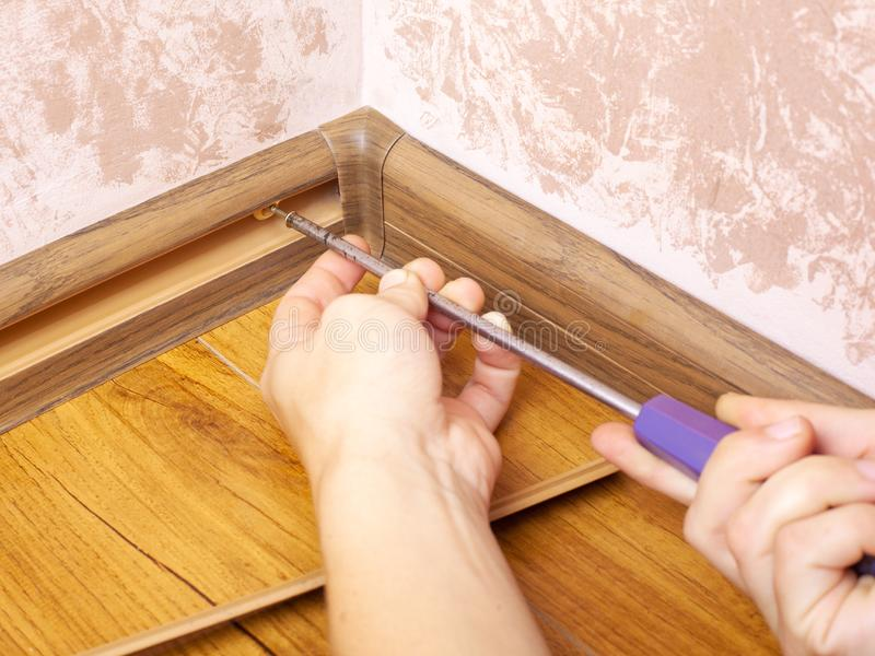 Installation and fixing of the baseboard,mounting and assembly plinth,the master screws the skirting board closeup.  stock photos