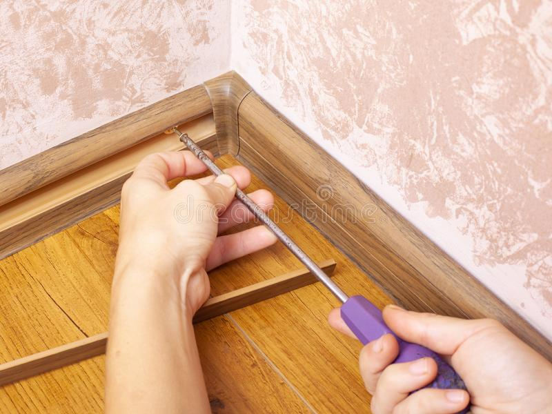 Installation and fixing of the baseboard,mounting and assembly plinth,the master screws the skirting board closeup.  royalty free stock photo