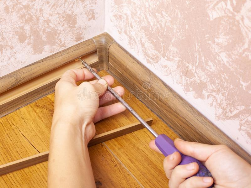 Installation and fixing of the baseboard,mounting and assembly plinth,the master screws the skirting board closeup.  royalty free stock images